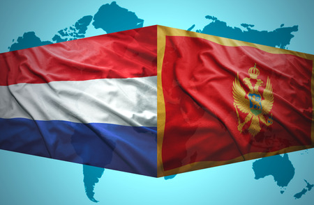 Waving Montenegrin and Dutch flags of the political map of the world photo