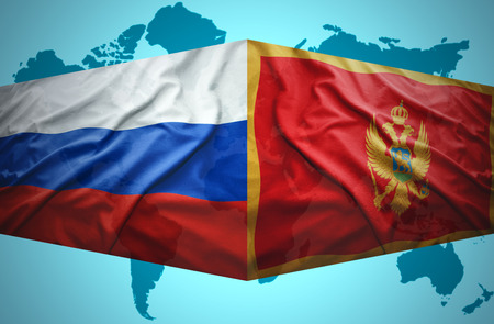 Waving Montenegrin and Russian flags of the political map of the world photo