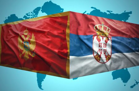 Waving Montenegrin and Serbian flags of the political map of the world photo