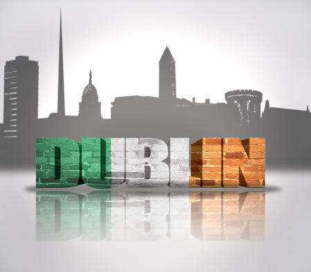 Word Dublin with national flag of Ireland near skyline silhouette photo