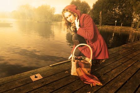 Little Red Riding Hood on a bridge near lake photo