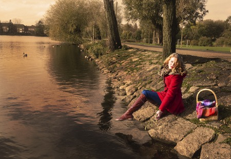 Beautiful girl in a red coat near the pond photo