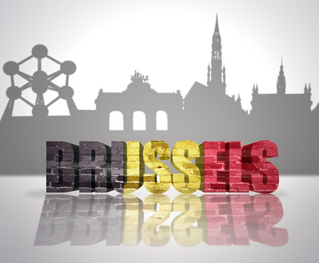 Word Brussels with national flag of Belgium  near skyline silhouette 免版税图像