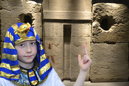 Egyptian boy farao in front of the ancient tombs photo