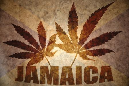 jamaican flag: text jamaica with cannabis leafs on a vintage jamaican flag background Stock Photo