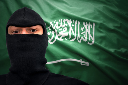 middle east crisis: dangerous man in a mask on a saudi arabia flag background