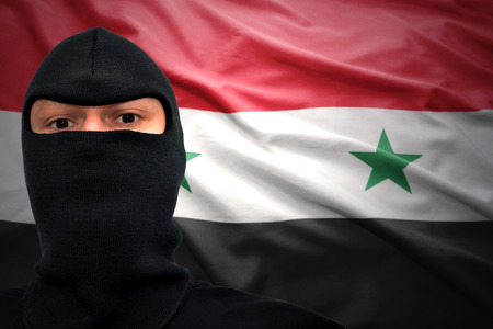 dangerous man in a mask on a syrian flag background photo