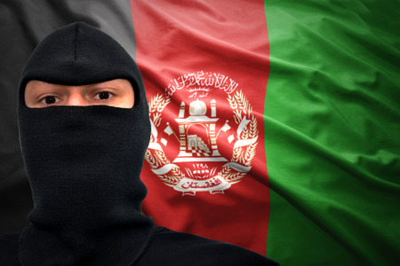 dangerous man: dangerous man in a mask on a afghan flag background