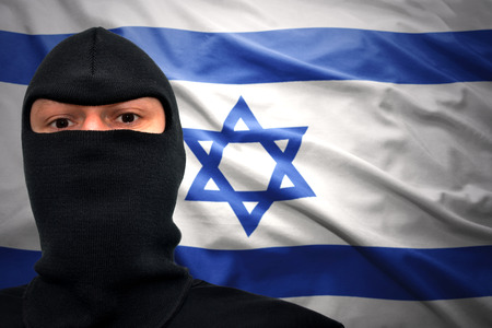 middle east crisis: dangerous man in a mask on a israeli flag background Stock Photo