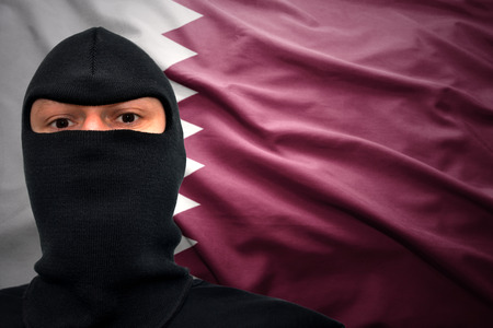 middle east crisis: dangerous man in a mask on a qatar flag background Stock Photo
