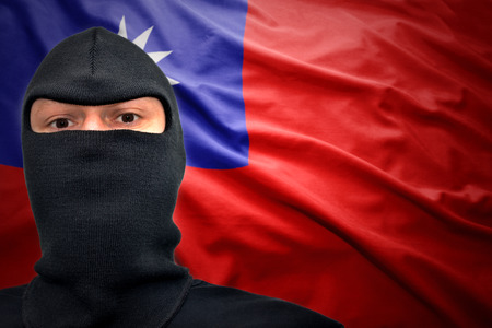 dangerous man: dangerous man in a mask on a taiwan flag background Stock Photo