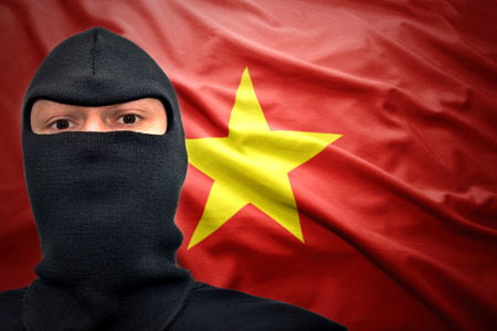 dangerous man: dangerous man in a mask on a vietnamese flag background