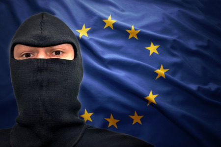 dangerous man in a mask on a european union flag background photo