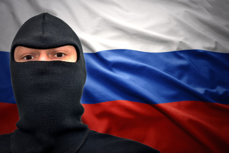 dangerous man in a mask on a russian flag background