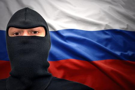 gevaarlijke man in een masker op een Russische vlag achtergrond