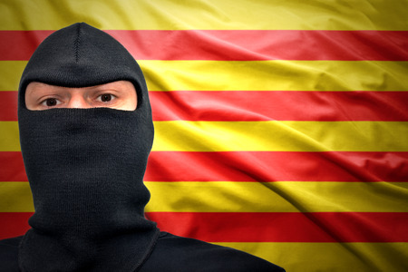dangerous man: dangerous man in a mask on a catalan flag background Stock Photo