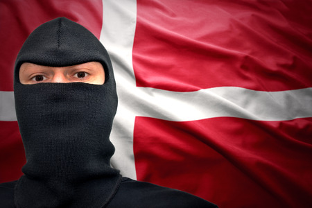 dangerous man: dangerous man in a mask on a danish flag background Stock Photo