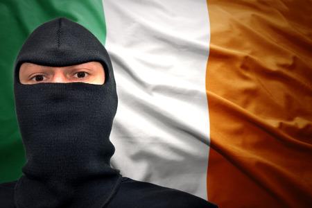 terrorism crisis: dangerous man in a mask on a irish flag background Stock Photo