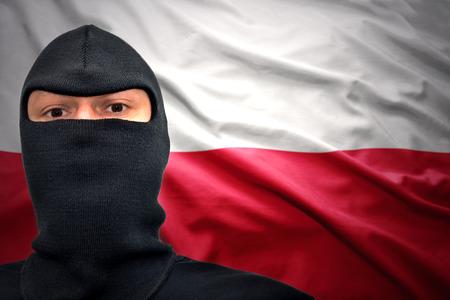 bandera de polonia: hombre peligroso en una m�scara en un fondo bandera polaca