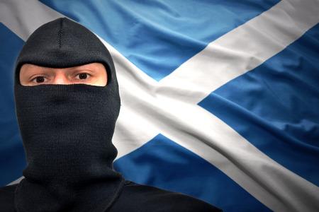 scottish flag: uomo pericoloso in una maschera su uno sfondo di bandiera scozzese Archivio Fotografico