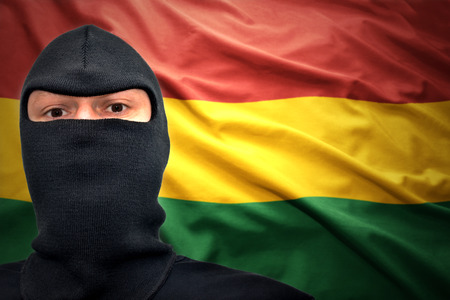 dangerous man in a mask on a bolivian flag background photo