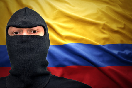 dangerous man: dangerous man in a mask on a colombian flag background