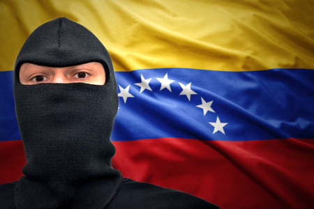 venezuelan: dangerous man in a mask on a venezuelan flag background Stock Photo
