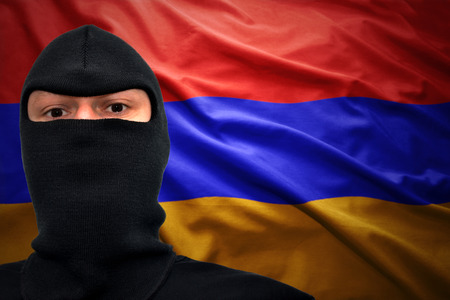 dangerous man in a mask on a armenian flag background Stock Photo