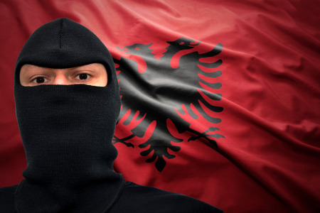 albanian: dangerous man in a mask on a albanian flag background