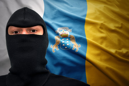 terrorism crisis: dangerous man in a mask on a canarian flag background