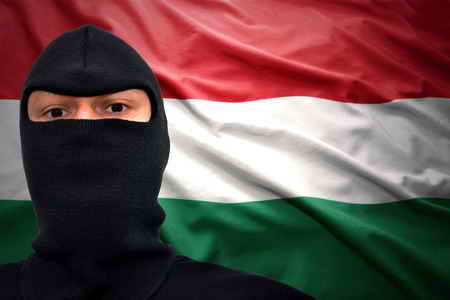 dangerous man: dangerous man in a mask on a hungarian flag background