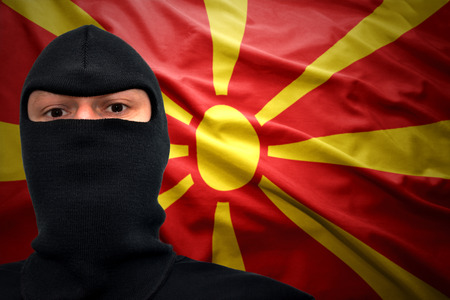 macedonian flag: dangerous man in a mask on a macedonian flag background Stock Photo
