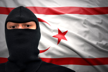 terrorism crisis: dangerous man in a mask on a northern cyprus flag background