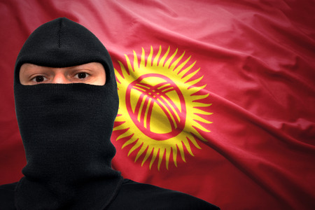 dangerous man: dangerous man in a mask on a kyrgyz flag background