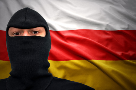 dangerous man: dangerous man in a mask on a south ossetia flag background