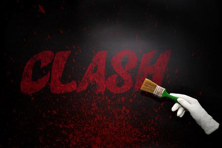 clash: mano a mano con el pincel pintar el choque texto en una superficie de color negro. concepto Foto de archivo