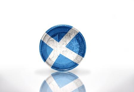 scottish flag: monete in euro con scozzese bandiera sul fondo bianco Archivio Fotografico