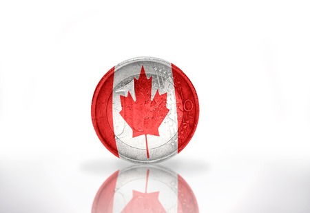 banderas americanas: moneda de euro con la bandera canadiense en el fondo blanco
