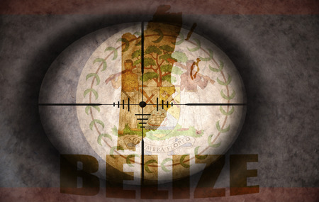 sniper scope aimed at the vintage belize flag and map photo