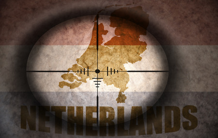 sniper scope aimed at the vintage netherlands flag and map photo