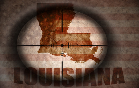louisiana flag: sniper scope aimed at the vintage american flag and louisiana state map