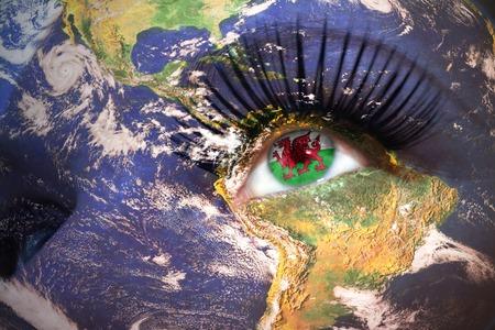 welsh flag: volto di donna con trama pianeta Terra e la bandiera gallese all'interno dell'occhio.