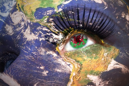 welsh flag: womans  face with planet Earth texture and welsh flag inside the eye.  Stock Photo