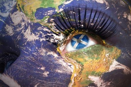 scottish flag: volto di donna con trama pianeta Terra e la bandiera scozzese all'interno dell'occhio. Archivio Fotografico