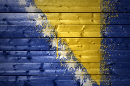 colorful painted bosnian flag on a wooden texture photo