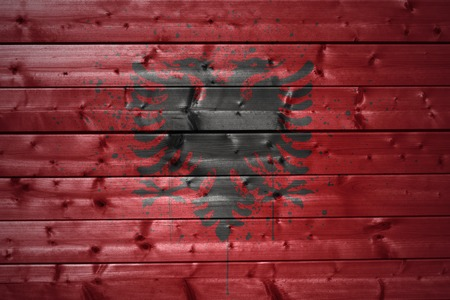 albanian: colorful painted albanian flag on a wooden texture