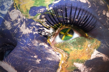 jamaican flag: womans face with planet Earth texture and jamaican flag inside the eye.