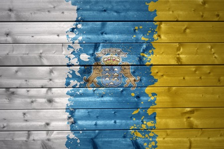 canarian: colorful painted canarian flag on a wooden texture