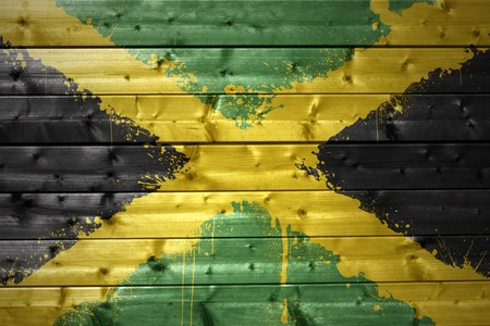 jamaican flag: colorful painted jamaican flag on a wooden texture
