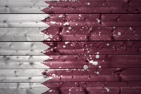 ancient near east: colorful painted qatar flag on a wooden texture